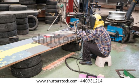 Welder  making aluminum rack