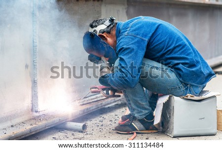 Welder man welding, spark, light and hot. Metal, iron work, and work. Mask and gloves for protection.