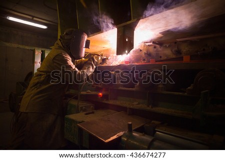 Welder repairing machinery at the plant of a Copper Mine in Chile