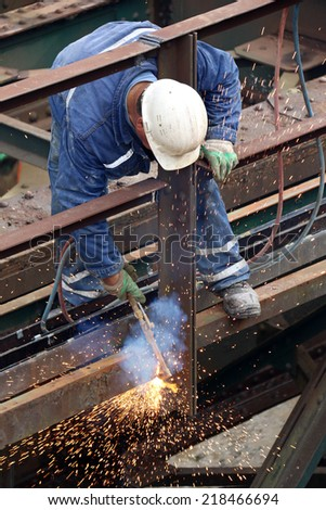 Welder using cutting torch to cut an old iron bridge