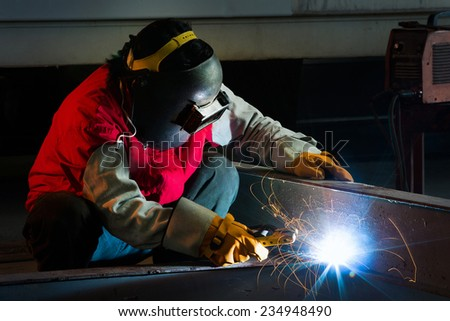 Welder welding a large piece in the factory - stock photo