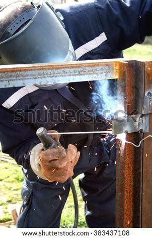 Welder welding a metal part wearing standard protection equipment - stock photo