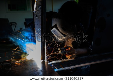Welder welding a steel structure in the factory