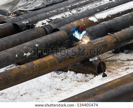 welder welds metal pipes in winter - stock photo