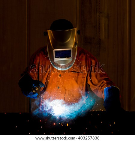 Welder with personal protective equipment and protective mask welding steel pipe in  factory. - stock photo