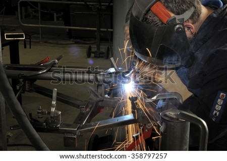 Welder with protective cap at work