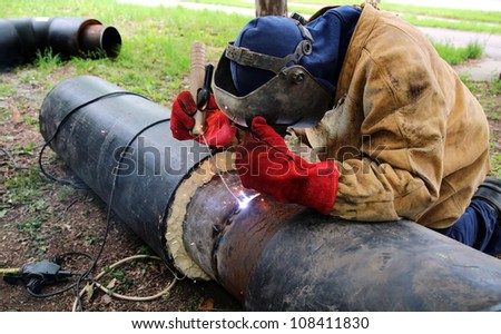 Welder with protective equipment welding outdoors.Selective focus. - stock photo