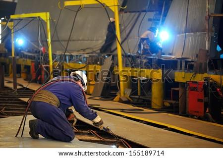 welder with protective mask welding metal - stock photo