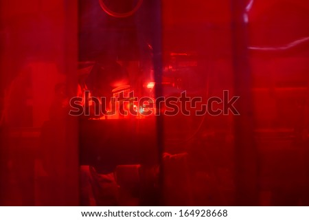 Welder with protective mask welding metal and sparks behind safety curtain - stock photo