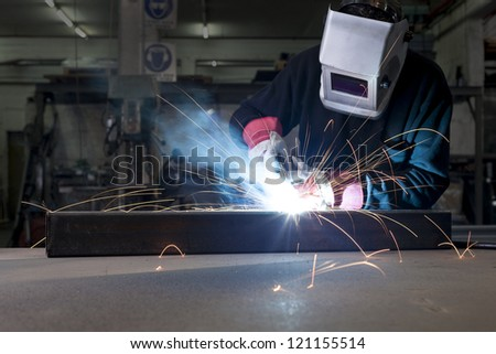 Welder with protective mask working in steel factory - stock photo