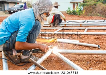 welder with turban is welding in Thailand. - stock photo