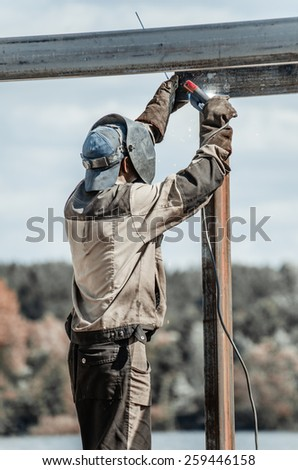 Welder worker in protective mask welding metal by electrode. - stock photo