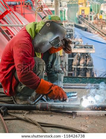 welder worker welding metal at construction site - stock photo
