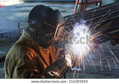 welder worker welding metal by electrode with bright electric arc and sparks during manufacture of metal equipment - stock photo
