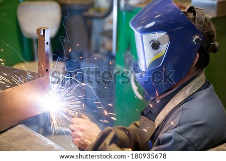 Welder working at factory workshop with flying sparks and smoke - stock photo