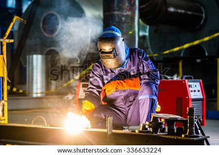 Welder working in an industrial setting manufacturing steel equipment - stock photo