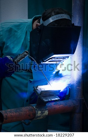 Welder working in the blue light of his torch. - stock photo