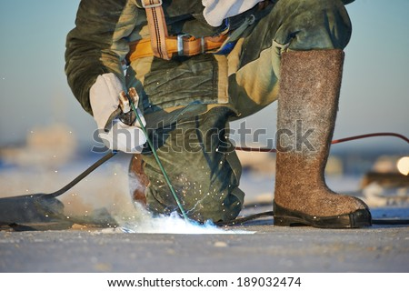 welder working with electrode at arc welding in construction site winter outdoors - stock photo