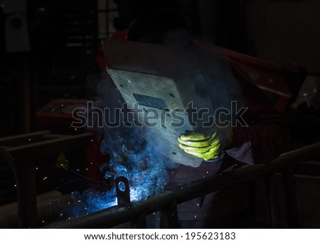 welder working with electrode at semi-automatic arc welding in