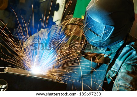 welder working with electrode at semi-automatic arc welding in manufacture production plant - stock photo