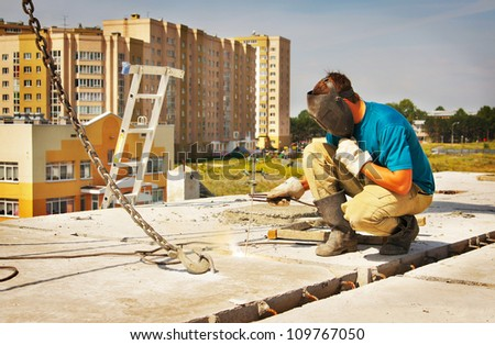 Welder works at the building of a house - stock photo