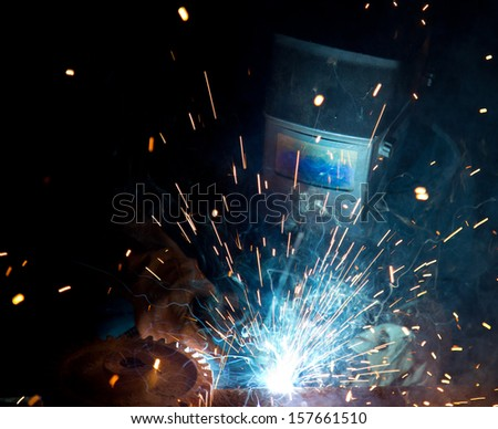 Welders in action with bright sparks. Construction and manufacturing theme. - stock photo