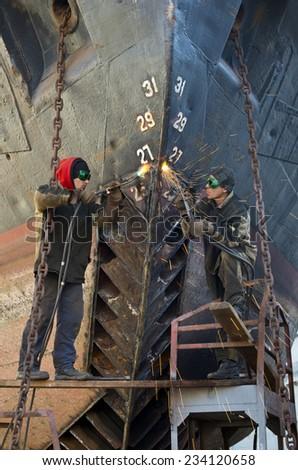 Welders on black metal, repairing a ship in dry dock - stock photo