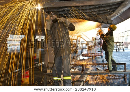 Welders on black metal, repairing a ship in dry dock