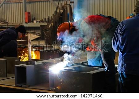 Welders work in the factory floor - stock photo
