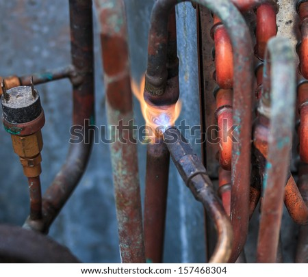 Welding copper pipes and Air conditioner repairman - stock photo