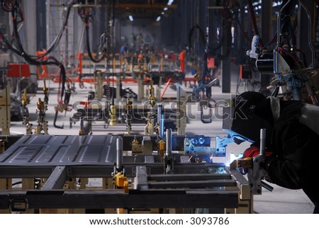 welding operator works with car details on factory - stock photo