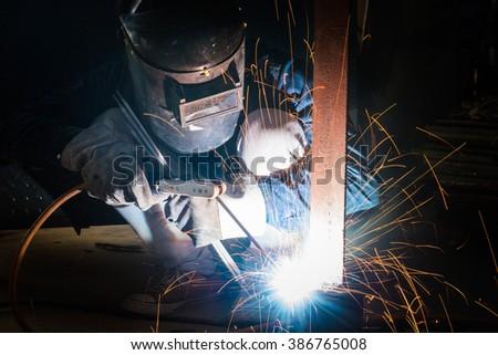 Welding skills training of welder with protective mask and welding steel metal part. - stock photo