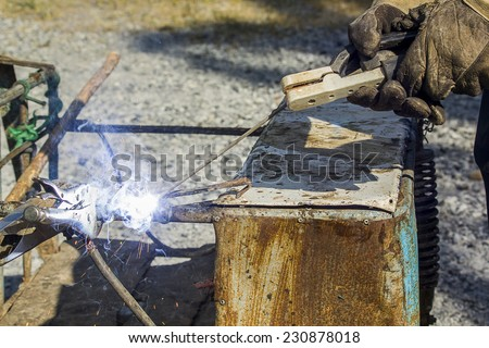 welding steel with sparks lighting.Daytime - stock photo