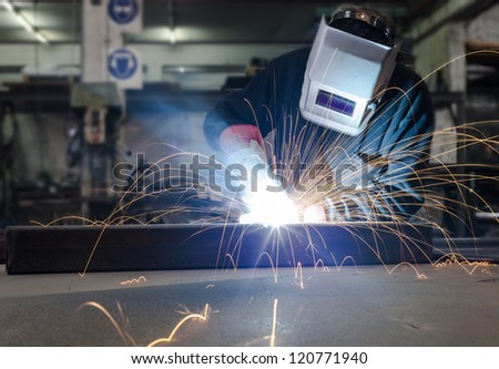 Welding with a lot of sparks in a metal industry factory - stock photo