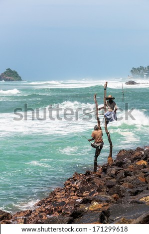 WELIGAMA, SRI LANKA - FEBRUARY 20: Asian men fishes in the traditional way while sitting on a pole on February 20, 2013 in Weligama, Sri Lanka. This type of fishing is traditional for south Sri Lanka. - stock photo