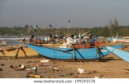 WELIGAMA, SRI LANKA - FEBRUARY 24: Local fishermen with their colorful fishing boats on the beach at Weligama, Sri Lanka on the 24th February, 2014. - stock photo
