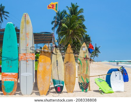 WELIGAMA, SRI LANKA - MARCH 5, 2014: Surf boards on sandy Weligama beach in Sri Lanka. On Weligama beach  surf is available all year around for beginner and advanced. - stock photo