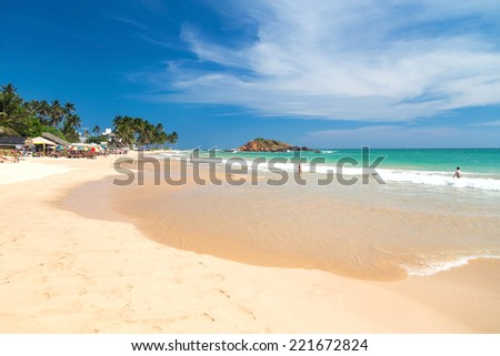 WELIGAMA, SRI LANKA - MARCH 5, 2014: Tourists on beautiful sandy beach. Tourism and fishing are two main business in this town. - stock photo