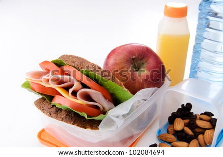 Well balanced packed lunch with gourmet sandwich, apple, nuts and orange juice - stock photo