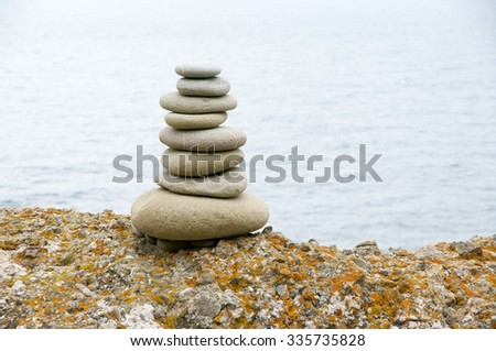 Well balanced stack of smooth pebble on rock against sea. - stock photo