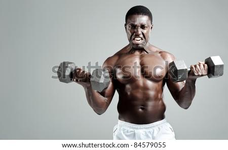 Well built muscular black man pumping iron - stock photo