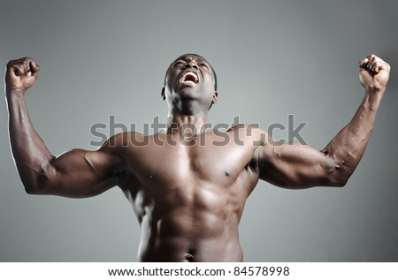 Well-built muscular black man with arms raised in studio - stock photo