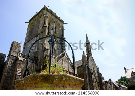 Well decorated with flowers at the square in front of Saint Ronan church in  medieval village Locronan. Brittany, France. - stock photo