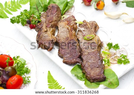 Well done angus beefsteak and salad on a white background