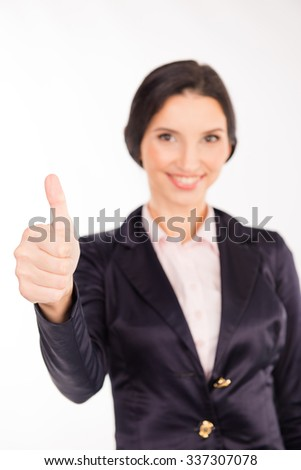 Well done! Beautiful young woman in formalwear showing her thumb up - stock photo