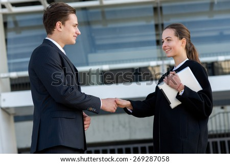 Well done business deal. Portrait of two confident and motivated partners. Man and woman are shaking hands, both have agreement on essential business project. Outdoor business concept - stock photo