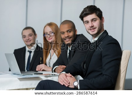 Well done business project. Portrait of confident and motivated businessman working on the project with his team with a smile. All are wearing formal suits. Office business concept