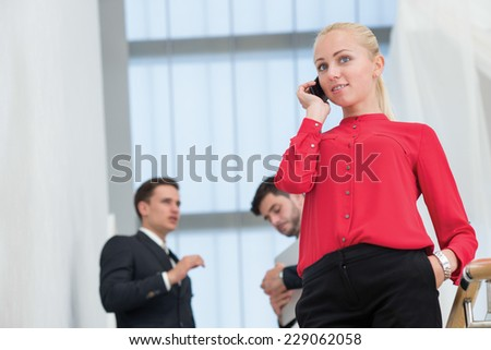 Well done by the mobile phone. Young motivated businesswoman is standing and talking on the mobile phone looking for a solution of her business issue. Two businessmen are behind on the background - stock photo