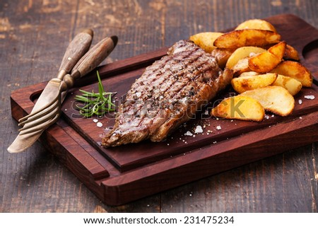 Well done grilled New York steak with roasted potato wedges on cutting board on dark wooden background - stock photo