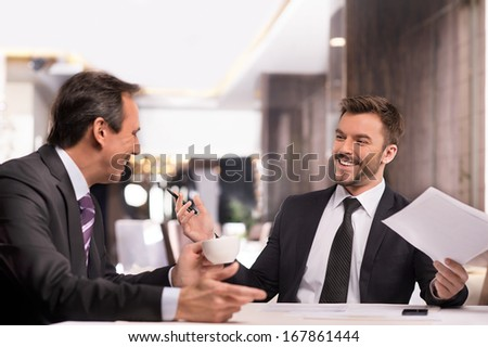 Well done! Two cheerful business people in formalwear discussing something and smiling while sitting at the restaurant - stock photo
